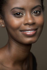 Close up beauty picture of a beautiful, young, black woman with a soft smile.