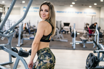 Young and beautiful Fitness trainer posing to the camera in the gym. Coach power