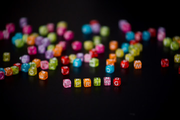 "Close-up word ""SPRING"" collected from colorful cubes with letters on black table with blurred background of cubes with letters scattered in chaotic manner"