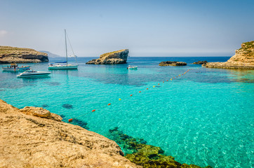 Blue Lagoon, Malta - the caves of the Blue Lagoon on the island of Comino on a bright sunny summer day with blue sky