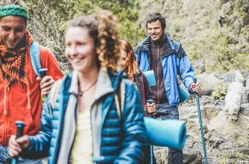 Young people doing trekking excursion in mountain's path - Hikers walking in nature path outdoor - Survival,travel and adventure concept - Focus on right man face Fototapete