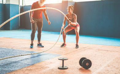 Fit woman with battle rope in functional training fitness gym