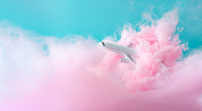 Passenger jet airplane flying through pastel pink clouds. Minimal transportation, travel or vacation concept.