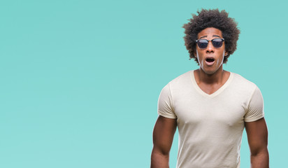 Afro american man wearing sunglasses over isolated background afraid and shocked with surprise expression, fear and excited face. Wall mural