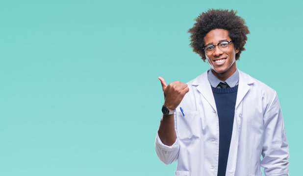 Afro american doctor scientist man over isolated background smiling with happy face looking and pointing to the side with thumb up.