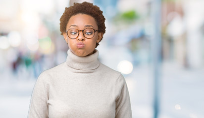 Young beautiful african american woman wearing glasses over isolated background puffing cheeks with funny face. Mouth inflated with air, crazy expression.