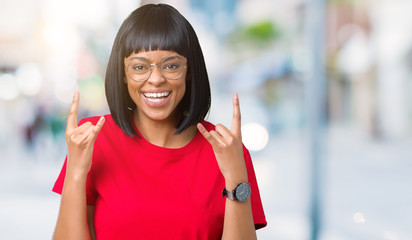 Beautiful young african american woman wearing glasses over isolated background shouting with crazy expression doing rock symbol with hands up. Music star. Heavy concept.