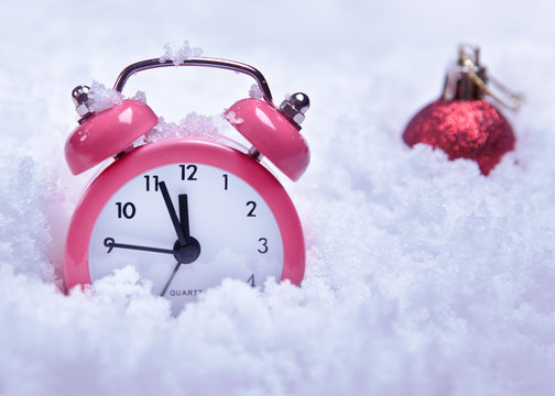 Round clock alarm clock in the snow next to the new year's red ball