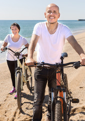 middle-aged man and woman with bicycles walking on the beach