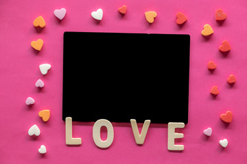 many hearts around Blackboard with word LOVE on pink background, Love icon, valentine's day, relationships concept with copy space