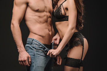 cropped view of woman undressing sexy shirtless man isolated on black