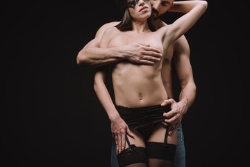 passionate man hugging attractive naked woman, isolated on black