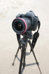 large professional camera stands on a tripod on the beach, blurry background