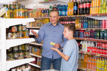 Man with son choosing goods together with shopping list