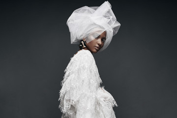 Fashion portrait of woman in white lace dress with white veil head tie and big earring. Studio, grey background