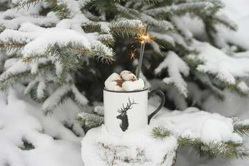 Drink with marshmallows in winter under the tree.