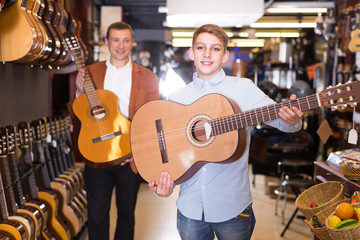 male seller showing acoustic guitar to boy client in musical shop