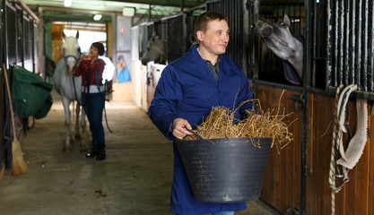 Man in working clothes feeding horse