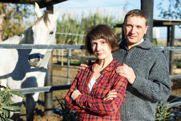 Portrait of couple standing at stable