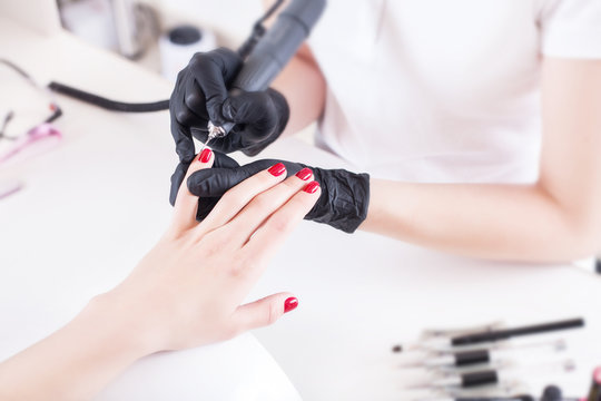 Manicurist, nail artist handles nails with manicure milling cutter. Beauty service, nail salon, health care and cosmetics.