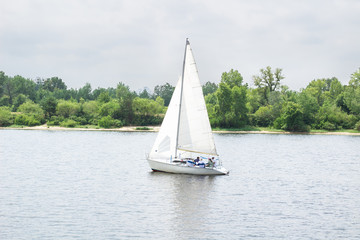 Sailboat yacht team sailing with full sails on river lake