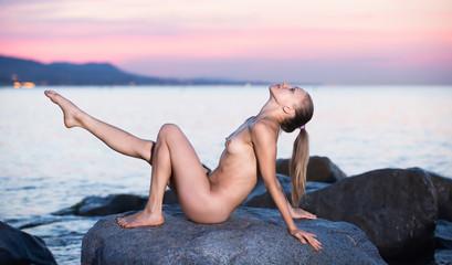 nude female doing yoga poses at  sunset sea shore