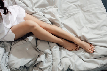 cropped shot of sensual young woman in white shirt resting on bed