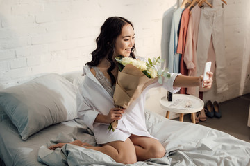high angle view of beautiful happy asian girl holding flower bouquet and taking selfie with smartphone in bedroom