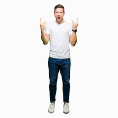 Handsome man wearing casual white t-shirt shouting with crazy expression doing rock symbol with hands up. Music star. Heavy concept.