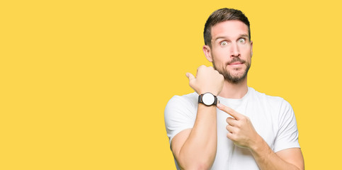 Handsome man wearing casual white t-shirt In hurry pointing to watch time, impatience, upset and angry for deadline delay