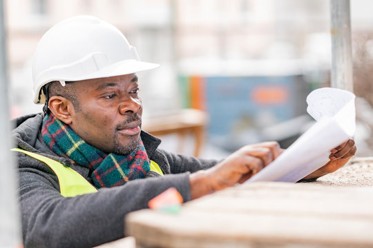 Profile portrait of an absorbed African American male engineer wearing safety jacket and helmet checking technical drawings and office blueprints among scaffolding