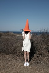 Woman with traffic cone standing against clear sky