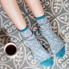 Low section of woman wearing socks while sitting beside coffee cup
