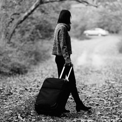 Side view of woman walking with luggage in forest