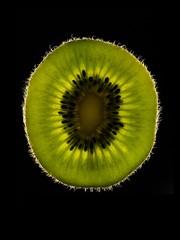 Slice of kiwi fruit against black background