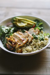 Close up of grilled chicken meat with vegetables and couscous served in bowl