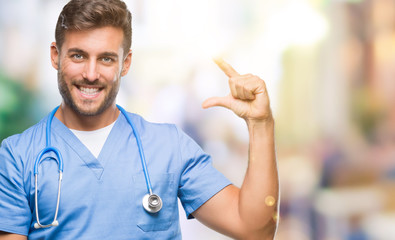 Young handsome doctor surgeon man over isolated background smiling and confident gesturing with hand doing size sign with fingers while looking and the camera. Measure concept.
