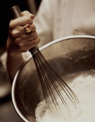 Close up of woman's hand whisking flour in bowl