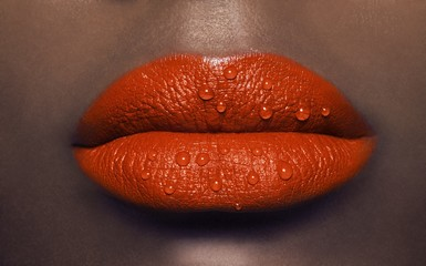 Close up of a woman's lips with orange lipstick