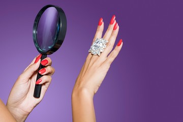 Woman's hands holding a diamond ring and magnifying glass