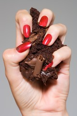 Close up of woman's hand crushing a piece of cake