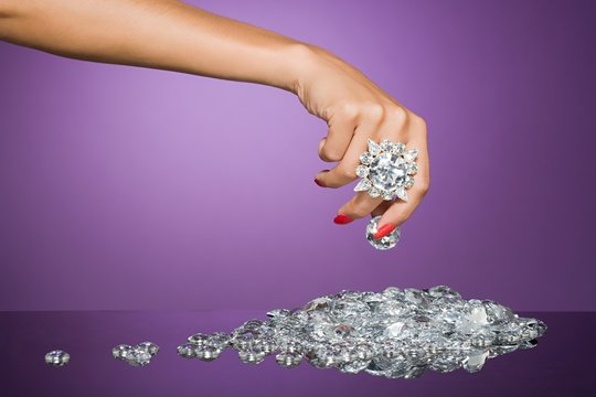 Close up of a woman's hand holding a large diamond