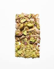 Crushed pistachios against white background