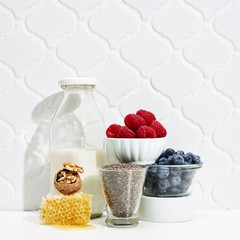 Milk with berries and ingredients against white background
