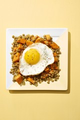 Half fried egg with carrot and legume served on plate