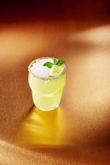 Drink with lime and basil against bronze background