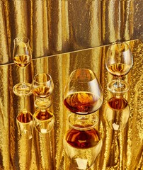 Close up of wine and champagne in glass against golden background
