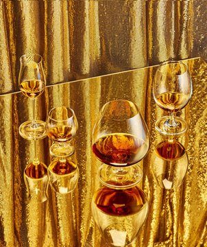 Close up view of wine and champagne in glass against golden background