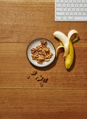 Overhead view of banana and walnut on wooden table