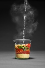 Hot water being poured in jar containing vegetables